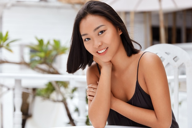 Positive lovely asian female with joyful expression dressed casually, sits in outdoor cafe, happy to have good service recreate with lover in tropical country during summer vacation. people, lifestyle