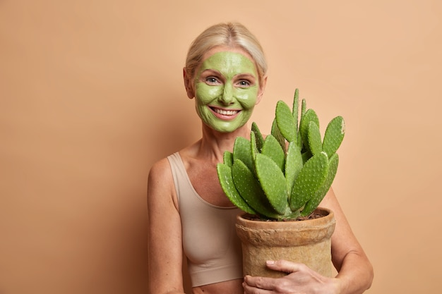 Positive lovely middle aged woman cares about skin applies green nourishing mask on face embraces pot with cactus smiles gently isolated over brown wall
