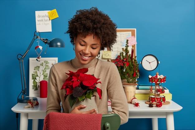 ポジティブな素敵な女性は、美しい赤い花で花瓶を抱きしめ、元気で、優しく微笑んで、キャビネットの中で居心地の良い家庭的な雰囲気を楽しんでいます