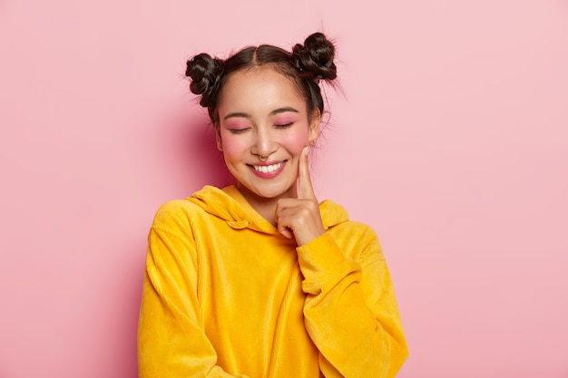 Positive lovely woman with pinup makeup, keeps index finger on cheeks, has eyes closed, dreams about something pleasant, wears yellow velvet hoody