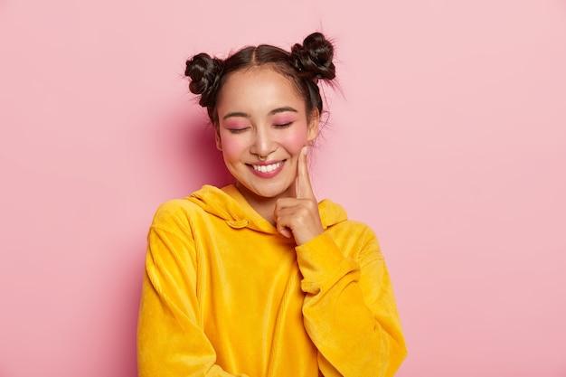 핀업 메이크업을 한 긍정적 인 사랑스러운 여성, 뺨에 검지 손가락을 유지하고 눈을 감고 즐거운 것을 꿈꾸며 노란색 벨벳 후드를 착용합니다.