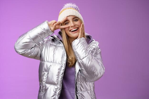 행복 하 게 웃는 하얀 치아를 즐기는 여행을 즐기는 은색 빛나는 재킷 모자 포즈에서 재미있는 겨울 휴가 긍정적 인 운이 귀여운 금발 소녀 눈 근처, 서있는 보라색 배경 평화 승리 기호를 보여줍니다.