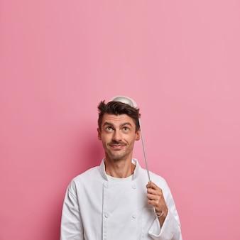 Lo chef maschio positivo posa con il mestolo sulla testa, va a preparare la zuppa, indossa l'uniforme bianca, tiene gli utensili da cucina, fa la cucina del ristorante, guarda sopra