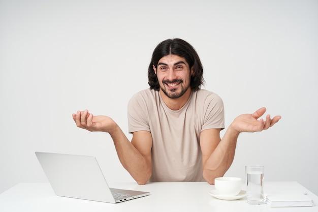 黒髪とあごひげを持つポジティブな男性、混乱した実業家。オフィスのコンセプト。職場に座って肩をすくめる。唇を噛む。白い壁に隔離