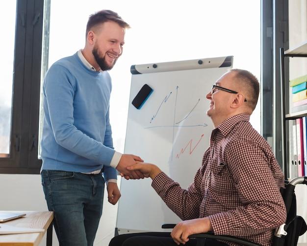 Uomo positivo che si congratula uomo disabile per il suo impegno