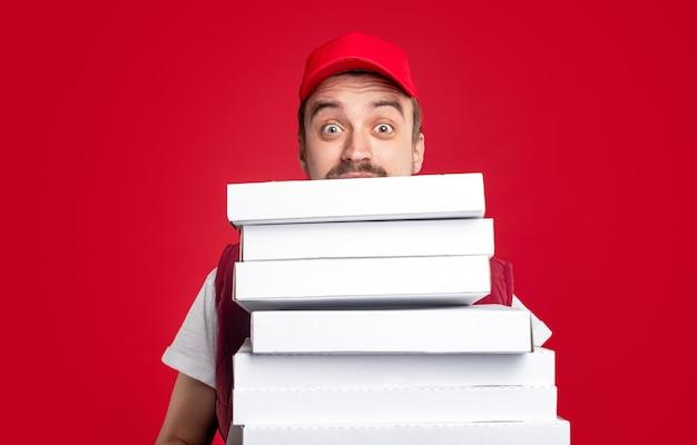 Положительный мужчина-курьер в красной кепке смотрит на стопку белых картонных коробок из-под пиццы, представляя службу доставки