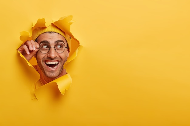 Viso maschile positivo che guarda curiosamente attraverso il foro della carta, tiene la mano sulla montatura degli occhiali, guarda da parte, indossa il cappello