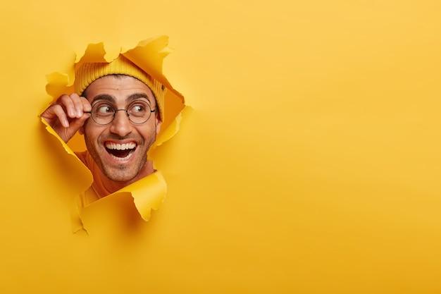 紙の穴を通して不思議なことに見て、眼鏡のフレームに手を保ち、脇を見て、帽子をかぶっているポジティブな男性の顔