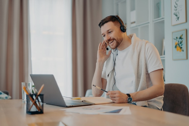 Positive male freelancer or student poses at home office wears headset takes part in education webinar makes notes looks gladfull at laptop display makes video call dressed casually. web communication