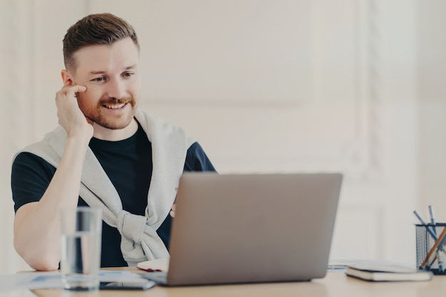 Positive male freelancer wearing casual clothes using earphones having online meeting, businessman smiling while sitting in front of laptop behind office desk and talking with colleagues online