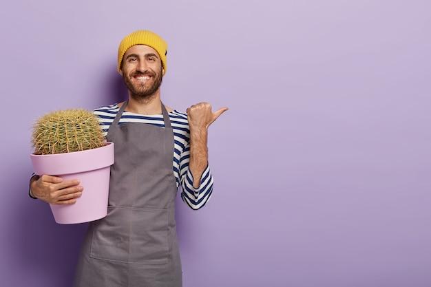 긍정적 인 남성 정원사는 엄지 손가락으로 멀리 가리키고 광고에 빈 공간을 표시하고 선인장 배경으로 냄비를 보유합니다.