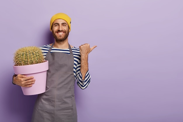 Positive male gardener points away with thumb, shows blank space for your advertisement, holds pot with cactusbackground