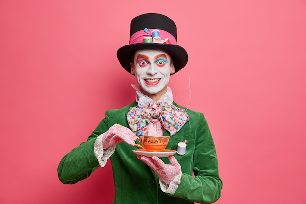 Positive male hatter enjoys tea party dressed in hat and green velvet jacket poses against rosy wall looks like real gentleman