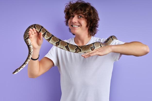 손에 뱀을 들고 긍정적 인 남성, 두려워하지 않고 공포증이 없습니다. 뱀과 함께 포즈를 취하는 흰색 티셔츠에 백인 남성