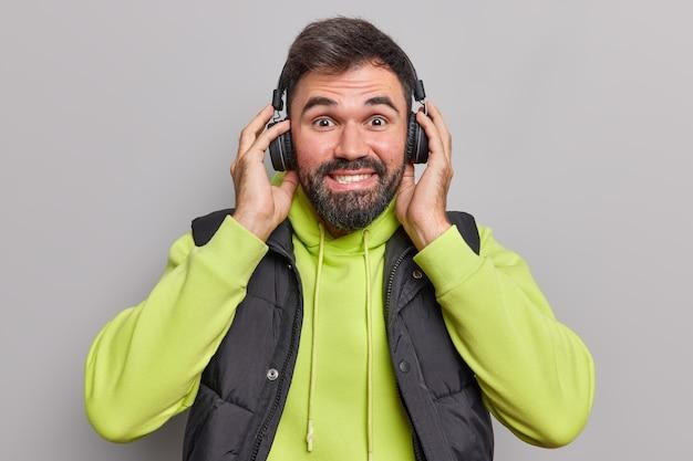 ポジティブな男性のメロディーは耳にワイヤレスヘッドホンをつけて音楽を聴き、お気に入りのプレイリストを楽しんでいます