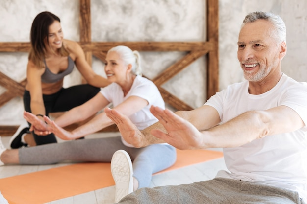 Positive male person keeping smile on his face while sitting on the floor on the foreground and doing exercises