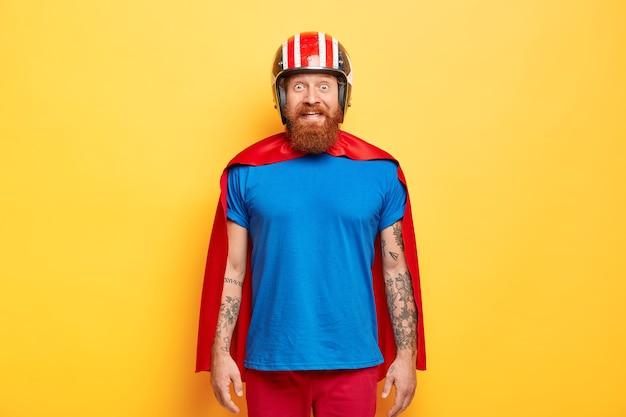 ポジティブな男性のスーパーヒーローは、ヘルメット、青いtシャツ、マントを着ています