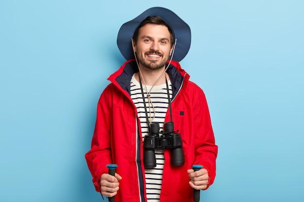 긍정적 인 남성 여행자는 숲을 걸을 때 트레킹 스틱을 사용하고, 휴가를 적극적으로 보내고, 긍정적으로 미소를 짓고, 세련된 모자와 빨간 재킷을 입고, 목에 쌍안경을 가지고 있습니다.