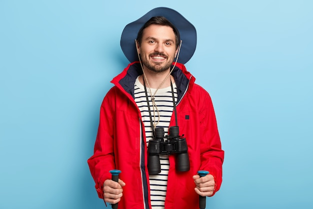 Positive male traveler uses trekking sticks for walking in forest, spends vacation actively, smiles positively, dressed in stylish headgear and red jacket, has binoculars on neck