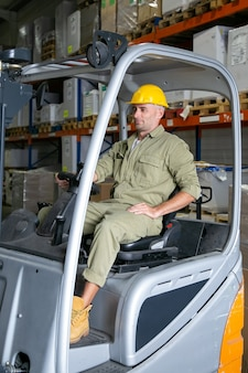Позитивный мужчина-складской рабочий в комбинезоне и каске водит вилочный погрузчик, держась за руль