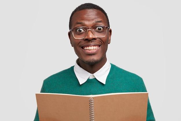 Studente maschio positivo vinto sorride positivamente, mostra denti bianchi, porta un taccuino a spirale aperto davanti, indossa gli occhiali, è di buon umore