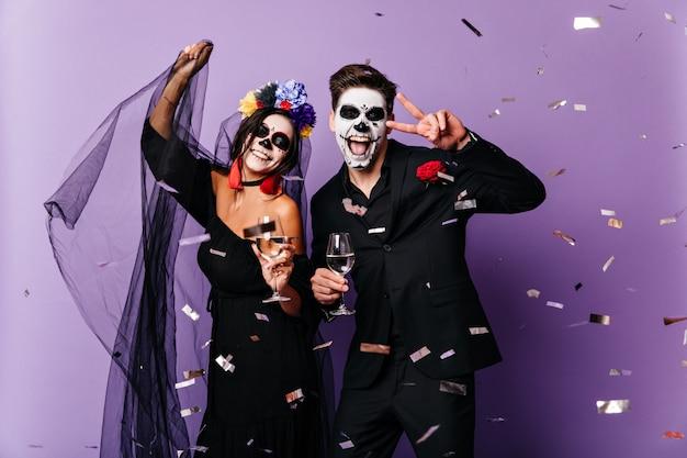 검은 옷과 가장 무도회 가면을 입은 긍정적 인 남녀는 할로윈 파티에서 색종이 조각 사이에서 춤을 추며 진심으로 기뻐하고 웃습니다.