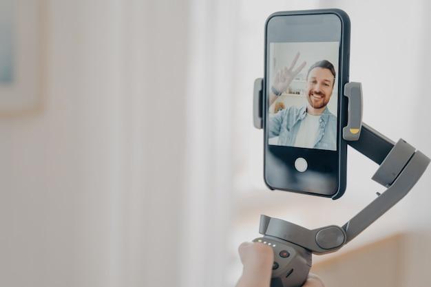 스마트폰으로 짐벌 안정기를 들고 집에서 거실에서 시간을 보내면서 셀카 사진과 라이브 비디오를 만들려고 하는 긍정적인 남자 블로거. vlog 및 비디오 블로깅 개념