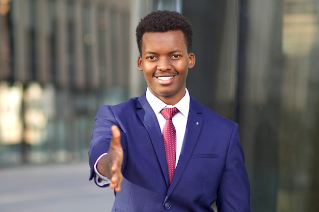 ポジティブな男性、フォーマルなスーツを着たビジネスマンが提案し、手を差し伸べ、ビジネスハンドシェイクのための手のひら、挨拶。開いた手を持つ若い黒人アフリカ系アメリカ人の男