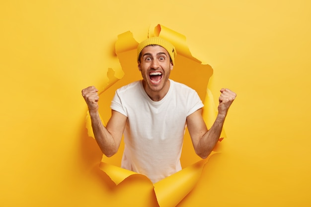 긍정적 인 남자는 주먹을 움켜 쥐고, 승리를 축하하고, 캐주얼 한 흰색 티셔츠와 노란 모자를 쓰고 있습니다.