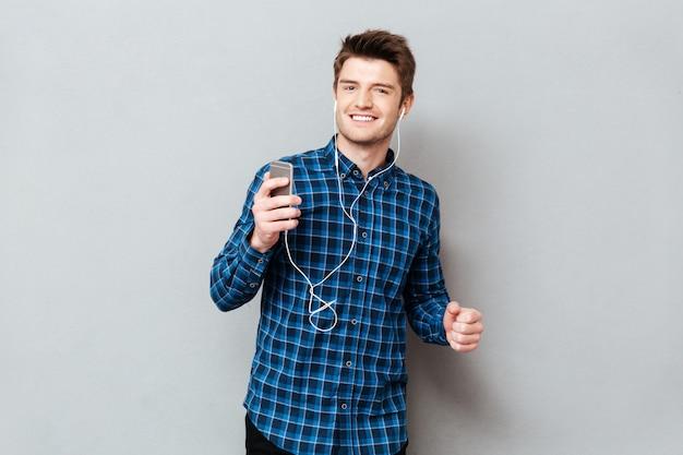 Dancing positivo dell'uomo mentre ascoltando musica sullo smartphone