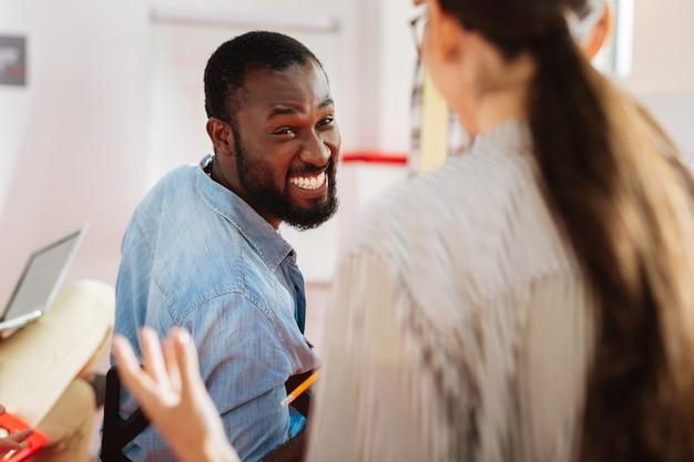 긍정적 인 사람. 토론에 적극적으로 참여하고 동료와 이야기하면서 웃고있는 흥분된 청년