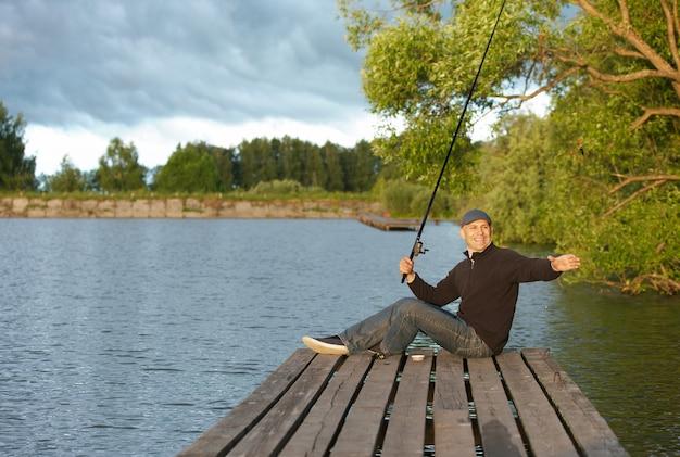 Позитивный человек, ловящий рыбу в пруду в солнечный день