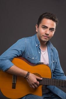 Положительный мужчина держит красивую гитару на черном фоне. фото высокого качества