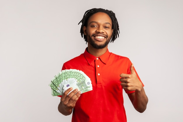 Positive man holding bunch of euro banknotes and showing thumbs up gesture, sign of success,
