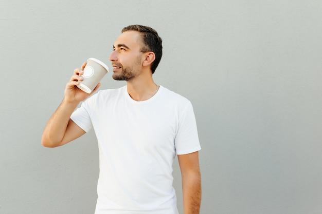 Позитивный мужчина держит бумажный стаканчик с кофе, изолированный над серой стеной