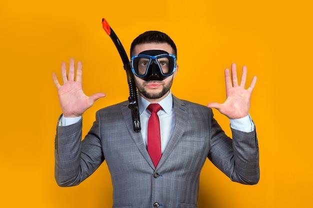 Позитивный мужчина в деловом костюме и водолазной маске на желтом