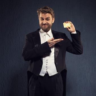 연미복을 입은 긍정적 인 남자가 신용 카드를 보여줍니다.