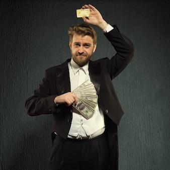 연미복을 입은 긍정적 인 남자는 신용 카드와 돈을 제공합니다.