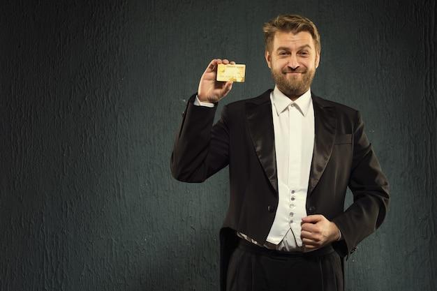 연미복을 입은 긍정적 인 남자가 신용 카드를 제공합니다.