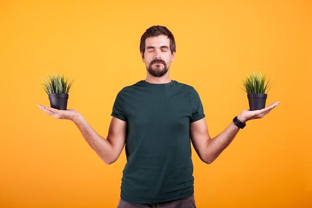 평온한 마음의 긍정적인 남자는 주황색 배경에 푸른 잔디가 있는 냄비 두 개를 가지고 있습니다. 자연 컨셉 사진과의 연결. 그의 눈은 감겨있다