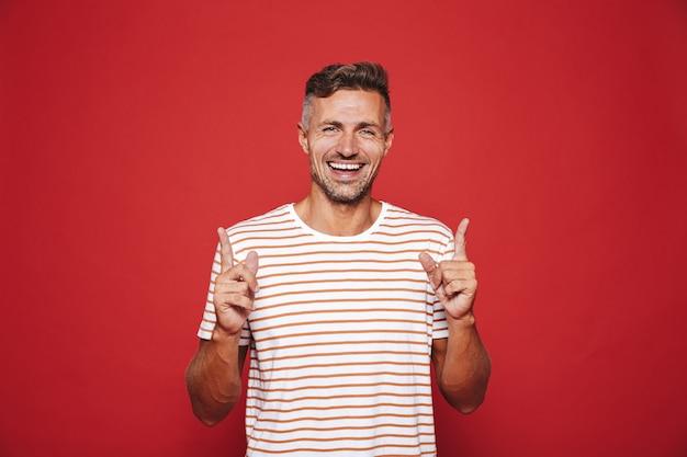 Позитивный мужчина в полосатой футболке показывает указательными пальцами вверх на copyspace, изолированном на красном