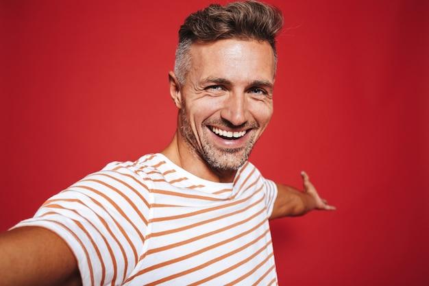 Позитивный мужчина в полосатой футболке улыбается и делает селфи на красном фоне