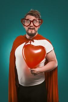 Позитивный мужчина в костюме супергероя и в форме сердца