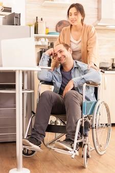 車椅子のポジティブな男とキッチンでラップトップを見ている妻。事故後に統合した歩行障害のある障害者麻痺障害者。