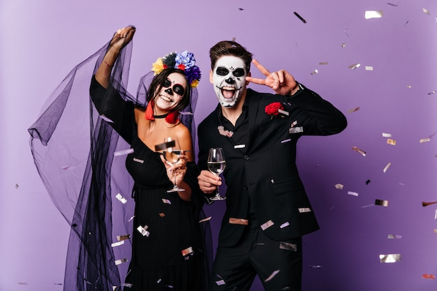 Positive man and lady in black clothes and masquerade masks sincerely rejoice and laugh, dancing among confetti at halloween party.
