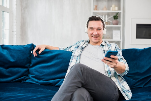 Positive man listening music in headphones and holding smartphone on sofa in room