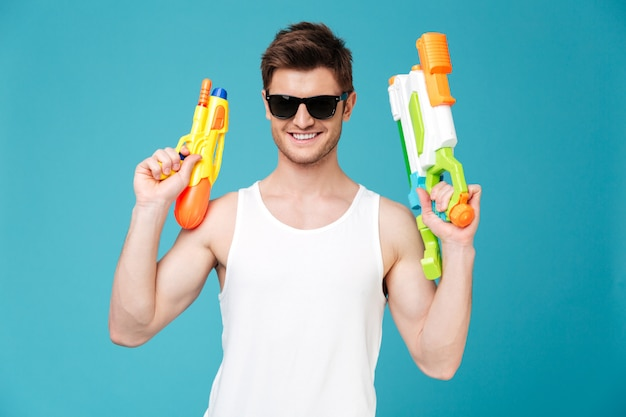 Positive man looking camera and holding two water guns
