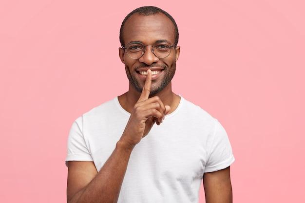ポジティブな男性は、静かなジェスチャーをし、白い歯を持ち、静かにして騒がないように頼み、一人で屋内に立ち、カジュアルな白いtシャツを着ています