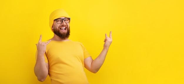 긍정적인 남자는 노란색 배경, 사람, 신체 언어 개념, 파노라마 레이아웃 위에 로큰롤 제스처를 만듭니다.