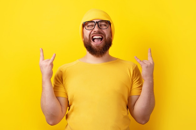 Positive man makes rock n roll gesture over yellow background, people and body language concept